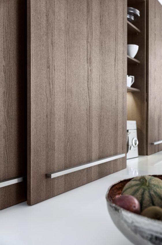 Вместо навесных шкафов здесь используется модуль с раздвижными дверями, который визуально составляет единое целое со столешницей.