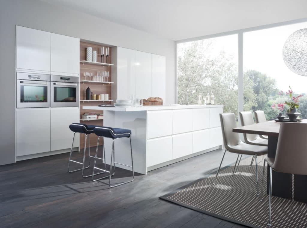 Для более официальных приемов можно использовать обеденный стол, который стоит отдельно. Вся необходимая техника встроена в высокие шкафы на высоте, удобной для использования, не занимая рабочего пространства.